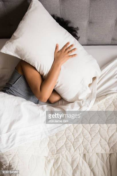 african american woman laying on bed hiding face under pillow - pillow stock pictures, royalty-free photos & images