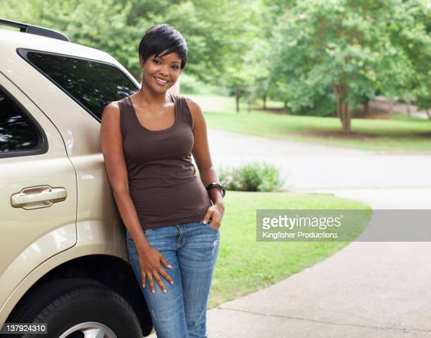 African American woman leaning on car in driveway