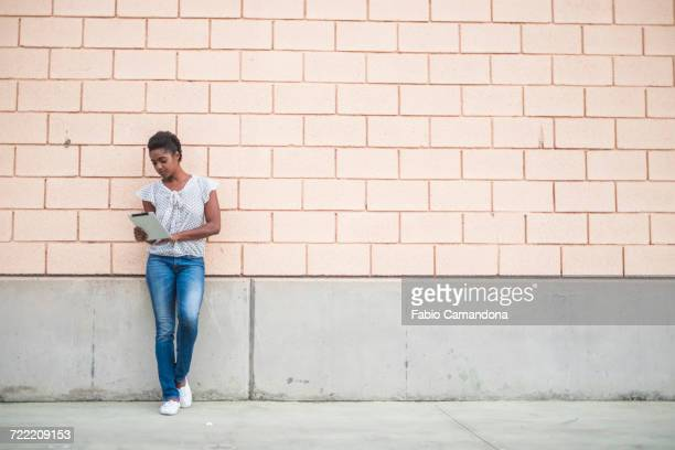 African American woman leaning on concrete wall using digital tablet