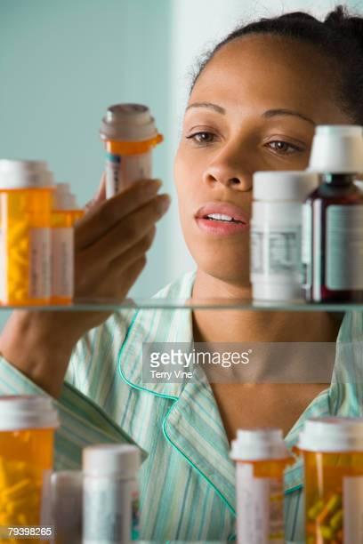 african american woman looking at medication bottle - armoire de toilette photos et images de collection