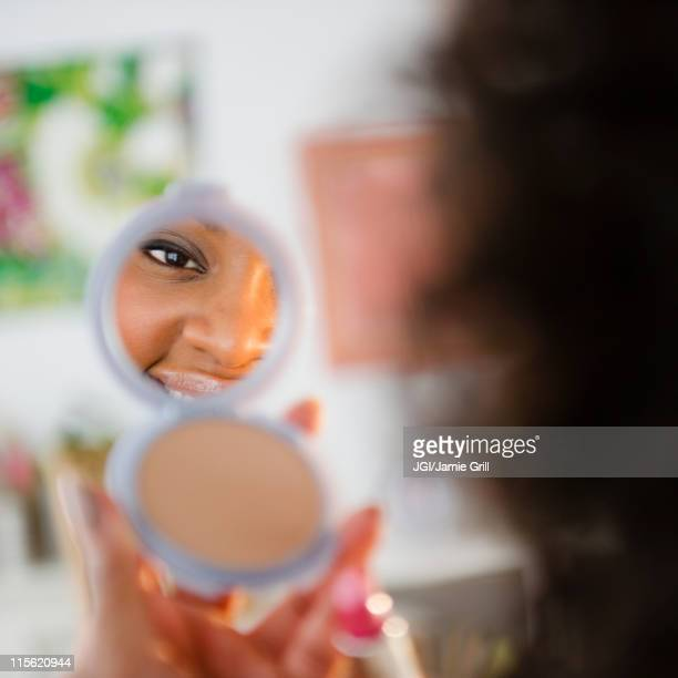 african american woman looking at reflection in compact - powder compact stock pictures, royalty-free photos & images
