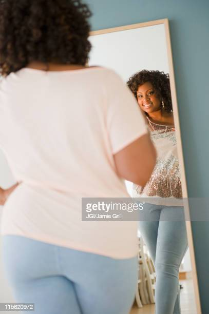 african american woman looking at reflection in mirror - chubby stock photos and pictures