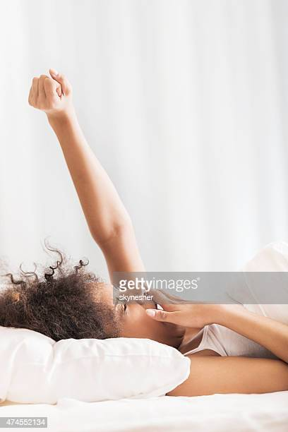 African American woman lying in bed and yawning.