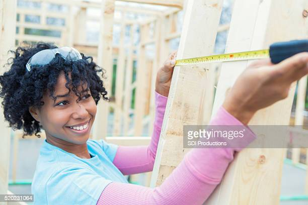 African American woman measures board on charity house