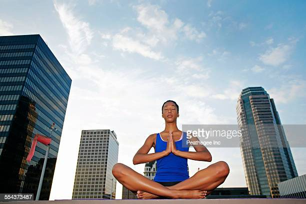 African American woman meditating on urban rooftop