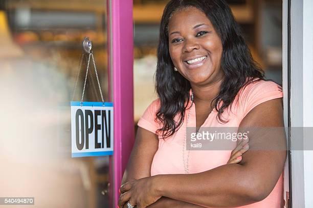 African American woman, OPEN sign on store door