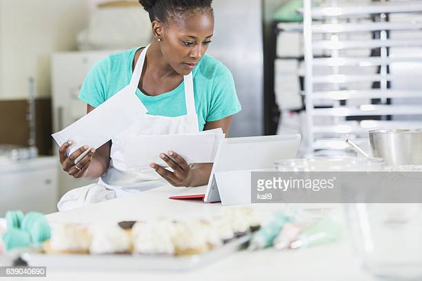African American woman, owner of bakery paying bills