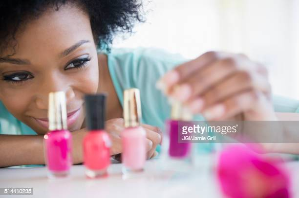african american woman painting her nails - マニキュア液 ストックフォトと画像