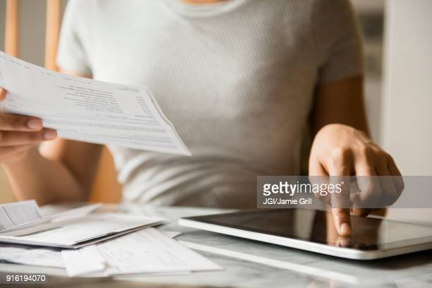 african american woman paying bills with digital tablet - financial bill stock pictures, royalty-free photos & images