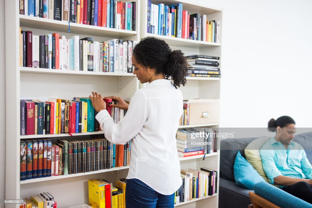 African American Woman Picking Up A Book From The Bookshelf Stock Photo