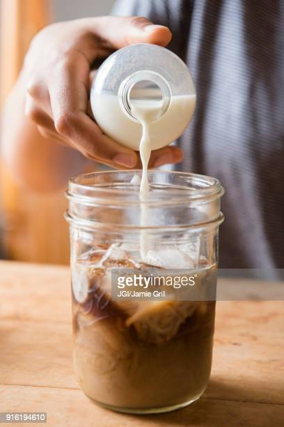 African American woman pouring milk into jar of coffee