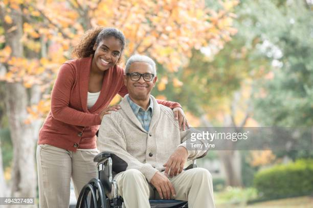 african american woman pushing father in wheelchair - leaning disability stock pictures, royalty-free photos & images