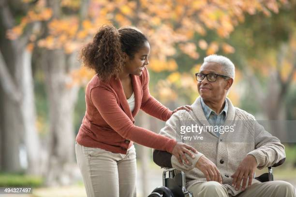 African American woman pushing father in wheelchair