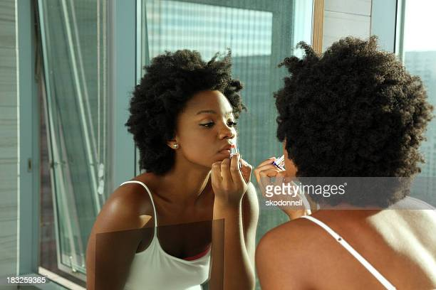 African American Woman Putting on Lipstick in a Mirror