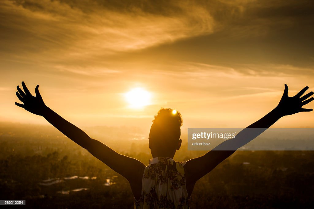 African American Woman Raising Arms at Sunset : Foto de stock