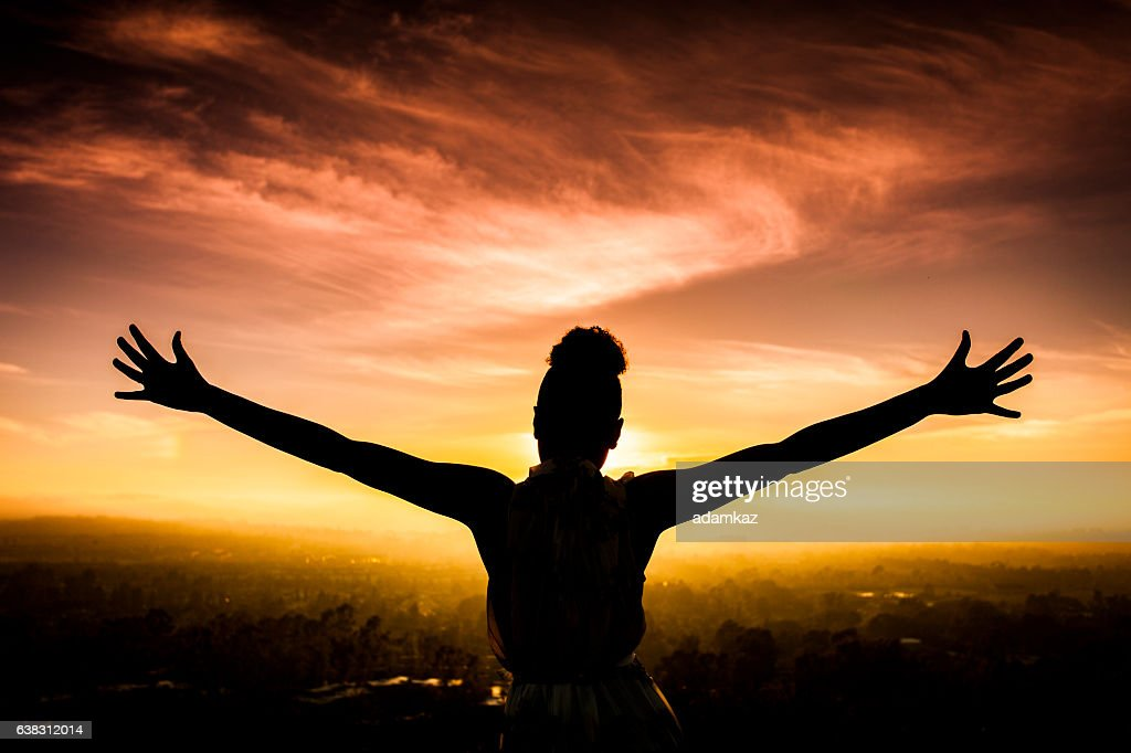 African American Woman Raising Arms at Sunset : Stock Photo