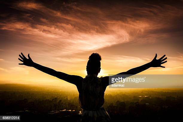 african american woman raising arms at sunset - spreading stock pictures, royalty-free photos & images