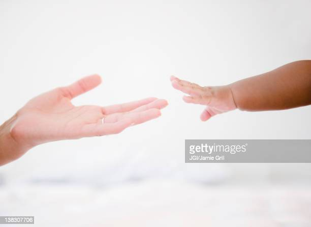 African American woman reaching out to baby boy