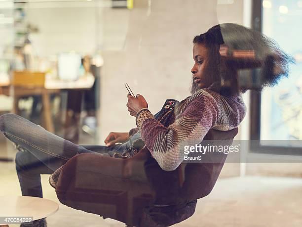 Mulher afro-americana a ler uma mensagem de texto no telefone móvel.
