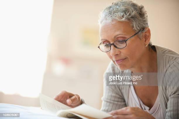 african american woman reading book - lunettes de lecture photos et images de collection