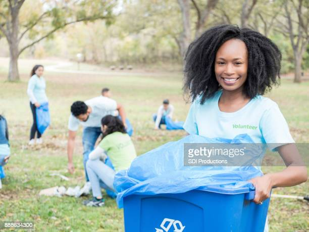 african american woman recycles during community cleanup - social awareness symbol stock photos and pictures