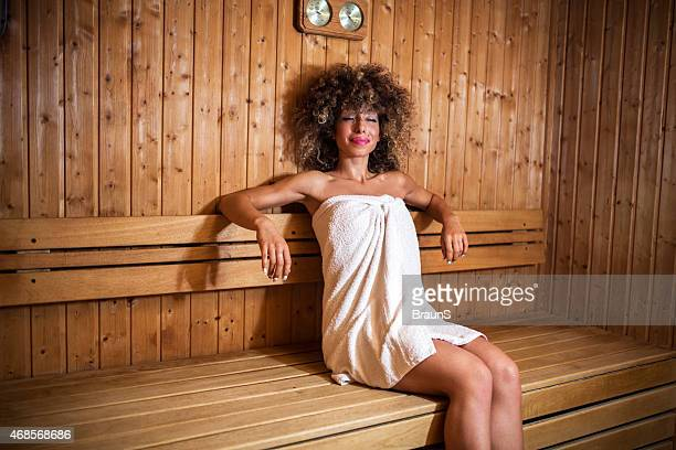 african american woman relaxing in sauna with her eyes closed. - black woman in sauna stock pictures, royalty-free photos & images