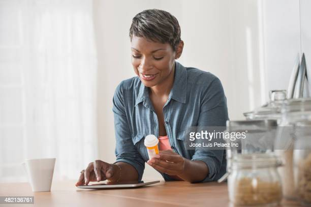 african american woman researching prescription bottle - 処方薬 ストックフォトと画像