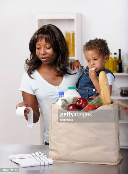 African American Woman Reviewing Receipt After Buying Groceries/ Shopping