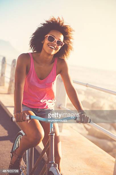 African american woman riding bike seaside