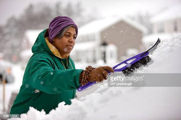 Femme afro-américaine à racler neige de pare-brise