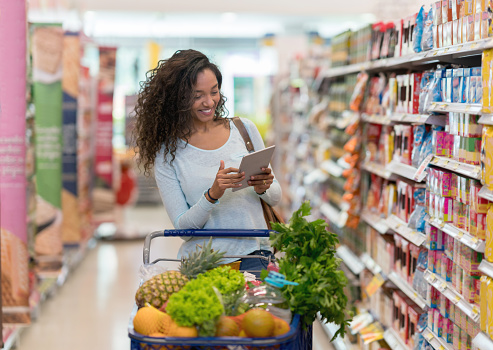 African american woman shopping at the supermarket and looking at the shopping list on a digital tablet - gettyimageskorea