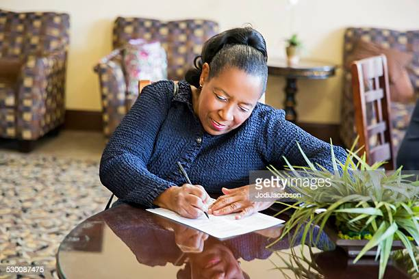 african american woman sitting at table completing job application - form filling stock pictures, royalty-free photos & images