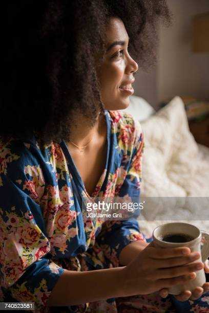 African American woman sitting in bed drinking coffee