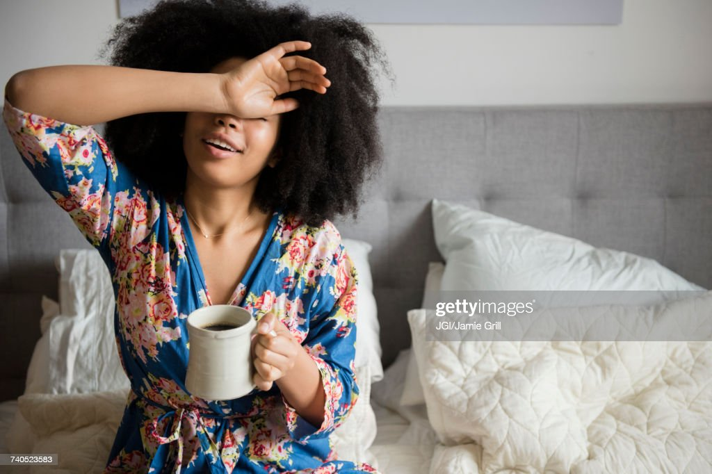 African American woman sitting in bed drinking coffee : Stock-Foto