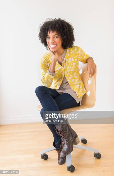 african american woman sitting in office chair - black boot stock pictures, royalty-free photos & images