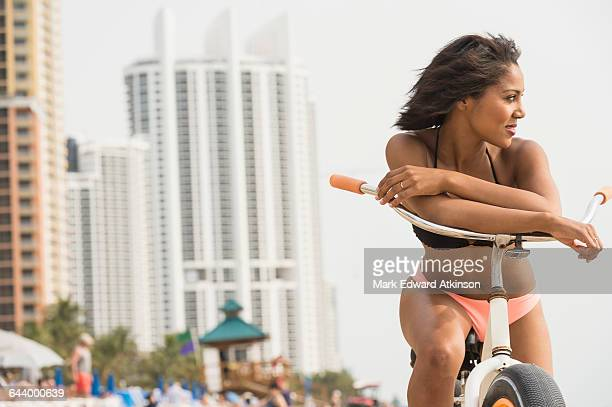 African American woman sitting on bicycle on beach
