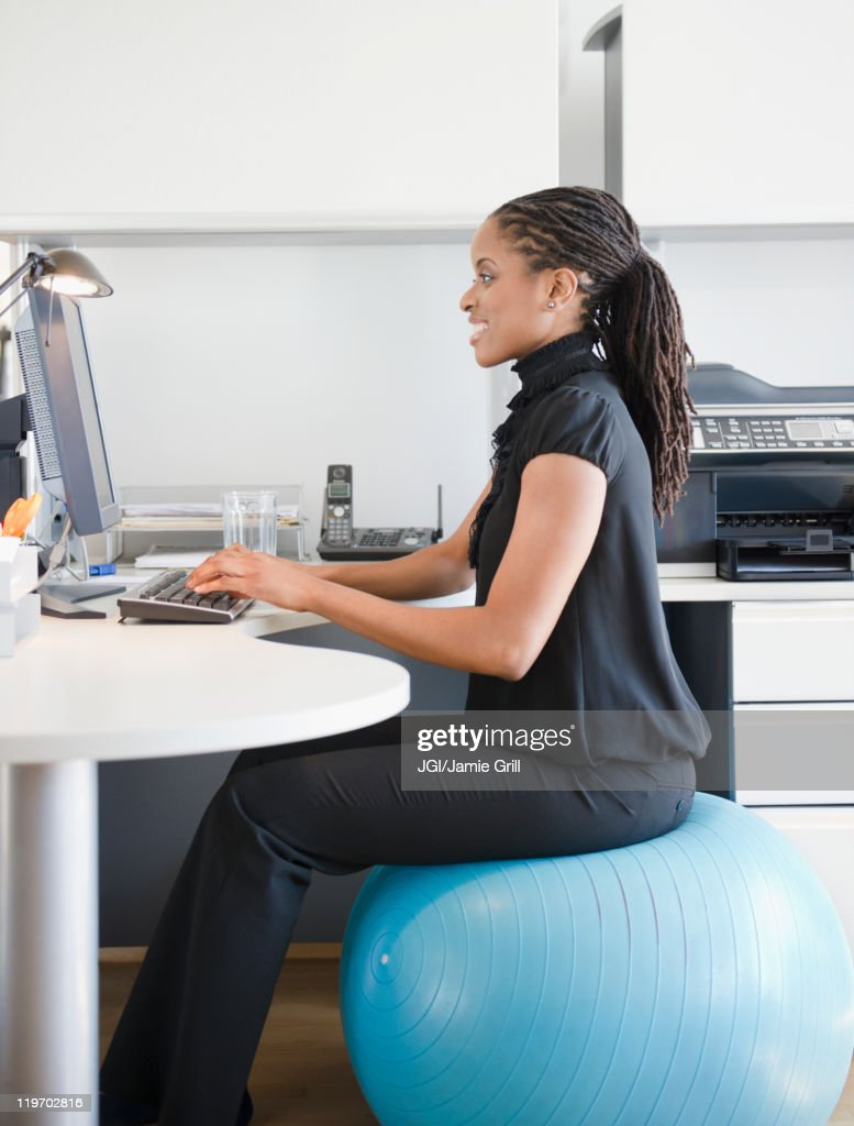 African American Woman Sitting On Exercise Ball At Desk Stock Photo