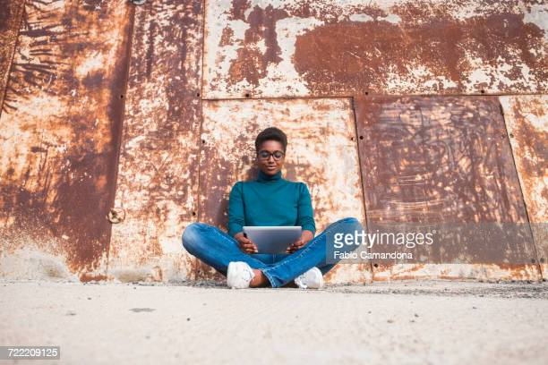 african american woman sitting on ground using digital tablet - metallic look stock pictures, royalty-free photos & images
