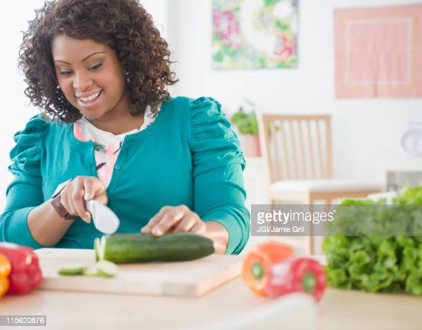 african american woman slicing vegetables - grasa nutriente fotografías e imágenes de stock