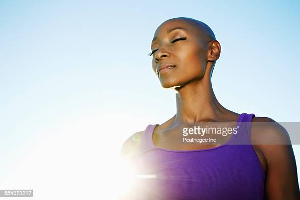 african american woman smiling in sunburst under blue sky - glattrasiert frau stock-fotos und bilder