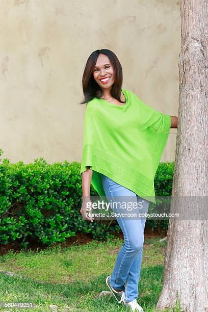 african american woman smiling near tree - nanette j stevenson stock photos and pictures
