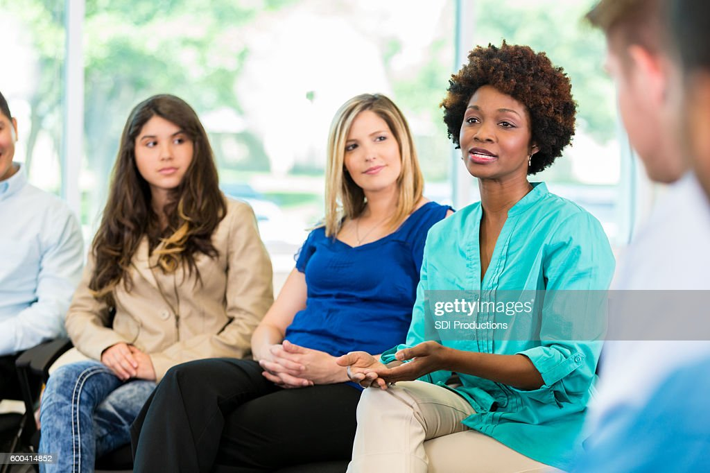 African American woman speaking during group therapy : Stock Photo