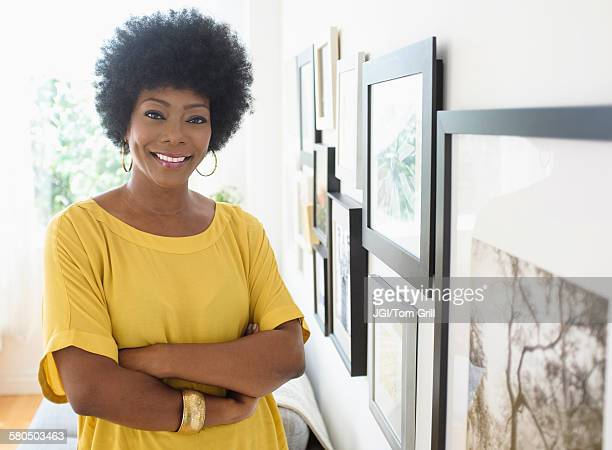 African American woman standing near pictures on wall