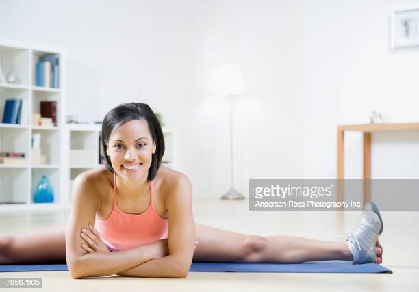 African American woman stretching on yoga mat