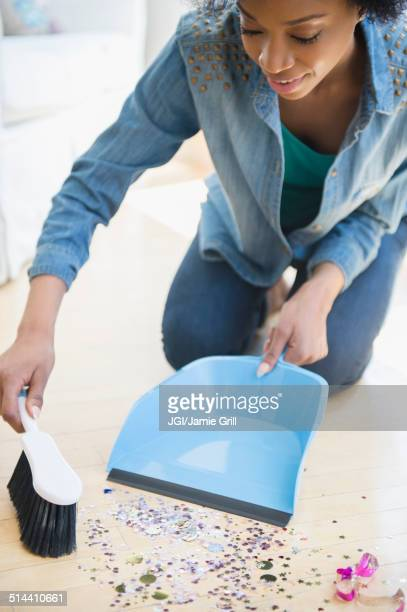 african american woman sweeping up confetti - cleaning after party bildbanksfoton och bilder