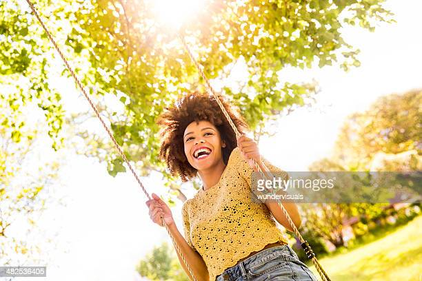 african american woman swinging on a rope swing