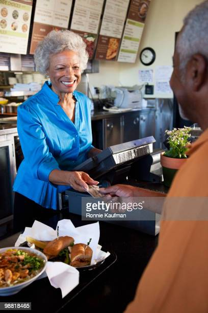 African American woman taking man's credit card in restaurant