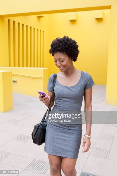 african american woman text messaging on cell phone in courtyard - grace kaufman stock pictures, royalty-free photos & images