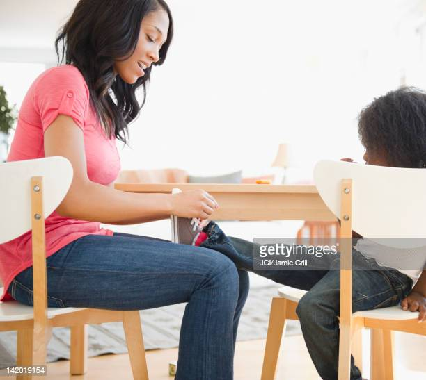 African American woman tying son's shoes
