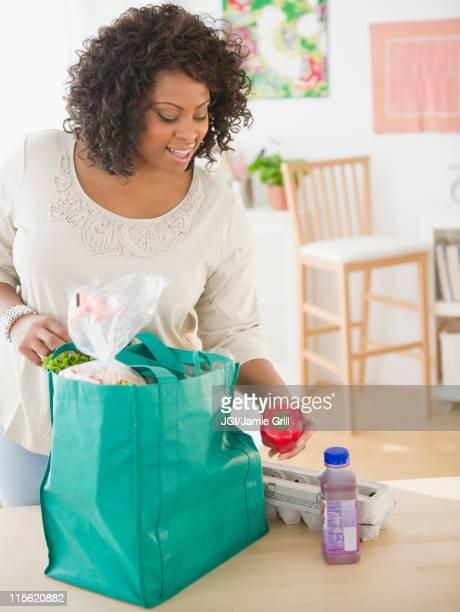 african american woman unloading groceries - 積荷を降ろす ストックフォトと画像